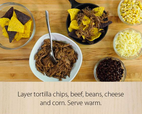 layer tortilla chips, beef, beans, cheese and corn